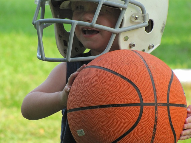 boy in football helmet holding basketball